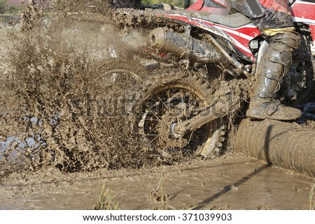 Enduro wheel in muddy track ,climb wood obstacle - stock photo