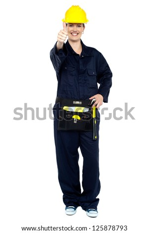 Energetic construction worker in yellow helmet showing thumbs up sign. - stock photo
