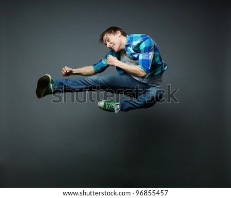 Energetic guy jumping with fists clenched tight and kicking the air - stock photo