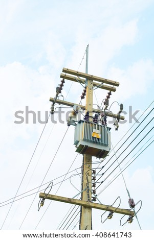 Energy and technology: electrical post by the road with power line cables, transformers and phone lines against bright blue sky providing copy space. electricity post in blue sky at Thailand.  - stock photo