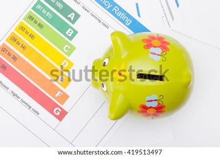 Energy efficiency chart and piggybank - studio shot from top - stock photo