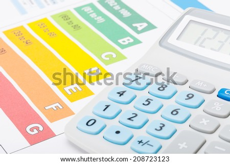 Energy efficiency chart with calculator over it - studio shot - stock photo