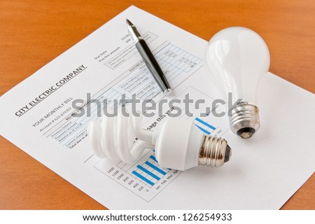 Energy efficient and incandescent  bulbs on electric bill. Energy efficient house concept. selective focus - stock photo