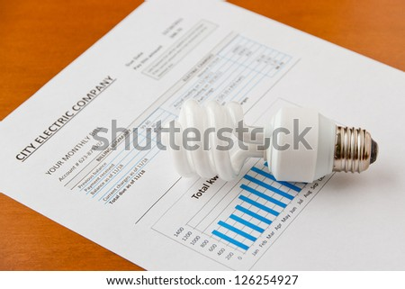 Energy efficient CFL bulb on electric bill. Energy efficient house concept.  selective focus - stock photo
