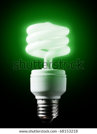 Energy-efficient  green bulb shining black background. - stock photo