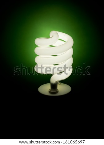 Energy efficient light bulb illuminating green - stock photo