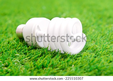 Energy efficient light bulb on green grass - stock photo