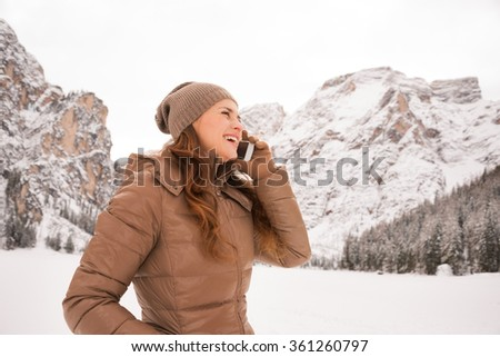 Energy-filling and exciting winter weekends in the mountains. Happy young woman talking cell phone outdoors among snow-capped mountains - stock photo