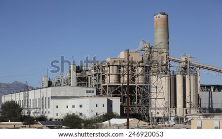 Energy production infrastructure with smoke pipe, elevator and power lines running through blue sky - stock photo