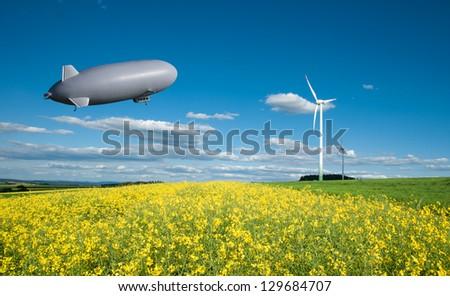 Energy, rape field and Zeppelin - stock photo