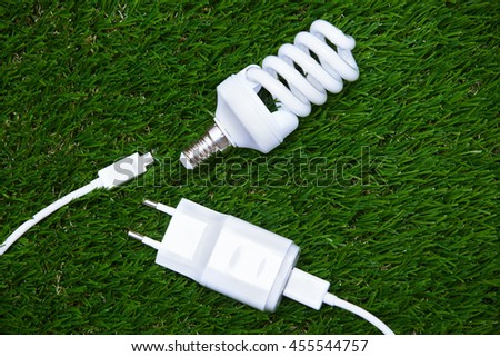 Energy saving bulb and electric plug in the grass - stock photo