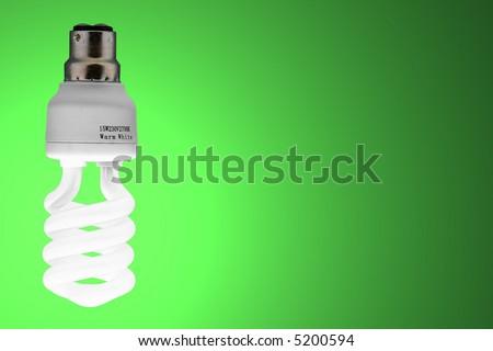 energy saving bulb on green backdrop - stock photo