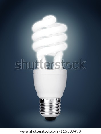 Energy saving fluorescent light bulb isolated on dark background. Clipping path included. - stock photo