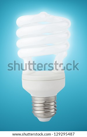 Energy saving fluorescent light bulb on light blue with clipping path - stock photo