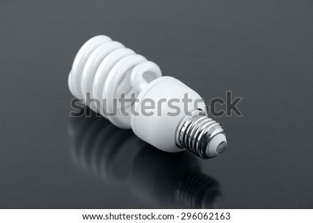 Energy saving fluorescent light bulb over grey background - stock photo