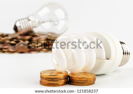 Energy-saving lamp and incandescent lamp lying on gold coins - stock photo