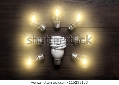 energy saving lamp in comparison with glow lamps concept - stock photo