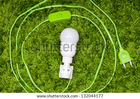 Energy saving lamp in the socket, with green wire, on the green carpet. - stock photo