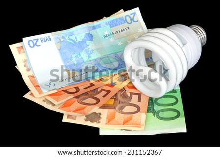 Energy saving light bulb and money ( euro banknotes) on the black background - stock photo