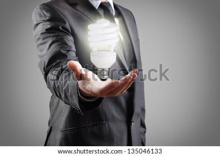 energy saving light bulb in hand of businessman - stock photo