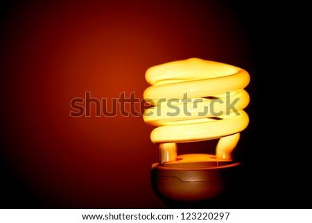 Energy saving light bulb on a red background. - stock photo