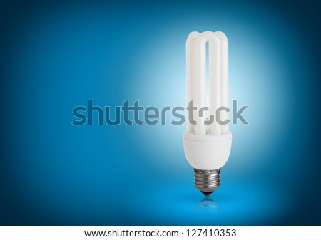 energy saving light bulb on blue background - stock photo