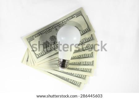 Energy saving - money. Led light bulb on the stack of dollars on a white background - stock photo