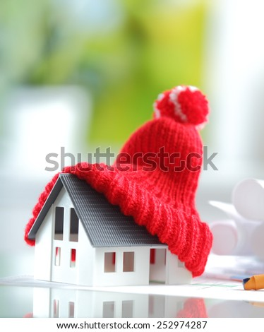 Energy saving Shot of Conceptual Red Knitted Hat on Top of Miniature House for isolation and insulation concepts - stock photo