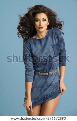 Energy woman in blue dress posing in studio - stock photo