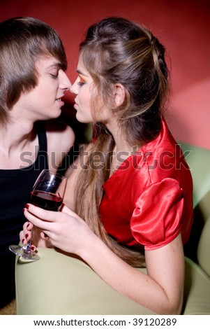 Engagement on sofa in red dark interior drinking shampagne, smile and embracing - stock photo