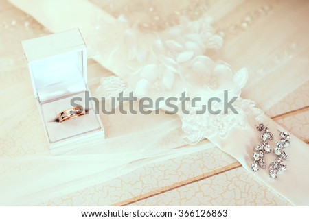 engagement ring in white wedding box with bride ear-rings on veil background - stock photo
