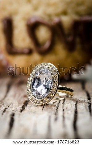 Engagement ring presented against the muffin with the word love written on it  - stock photo