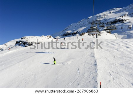 Engelberg, Switzerland - 18 February 2015: People skiing and going up the mountain by chairlift at Engelberg on the Swiss alps - stock photo