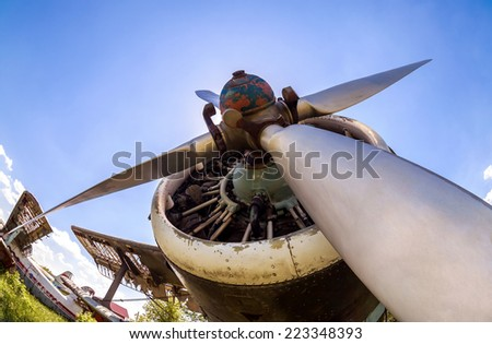 Engine and propeller of vintage aircraft against blue sky - stock photo