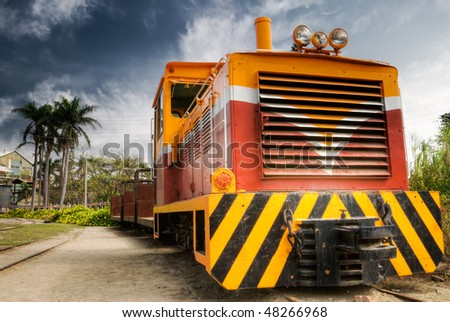 Engine of old train under dramatic sky. - stock photo