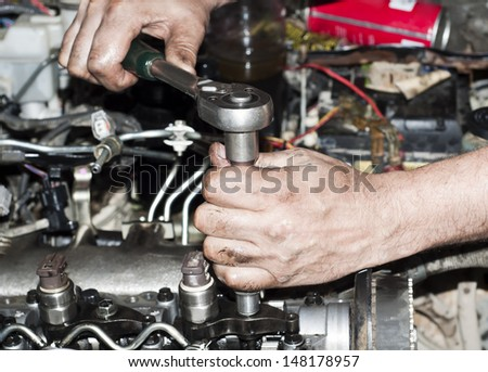 Engine repair close up. In hands tool. - stock photo
