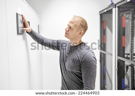 Engineer adjusts air conditioner in datacenter - stock photo