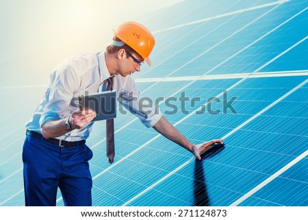 Engineer at solar power station with solar panel tablet checks.  - stock photo