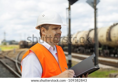 Engineer at the station near the wagons - stock photo