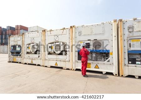 Engineer checking equipment in control system of reefer container box at yard - stock photo