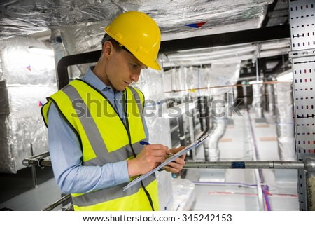 Engineer checking the temperature pipes in the control room - stock photo