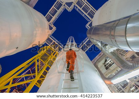 Engineer climb up to oil and gas process plant to observer gas dehydration processing and survey abnormal condition in night shift - stock photo