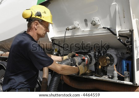 engineer connecting pipeline nozzle to oil-tanker, close-ups - stock photo