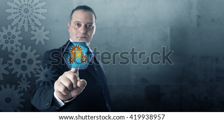 Engineer connecting to a virtual gear drive via a push button displaying cog wheels. Business process management metaphor and industrial technology concept. Plenty of copy space over gray stone wall.  - stock photo