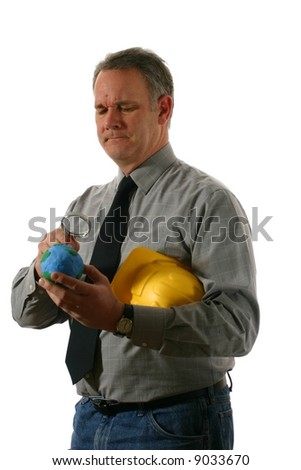 Engineer examining the earth with a concerned expression on his face - stock photo