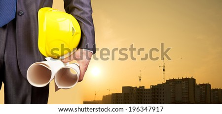 engineer hand holding yellow helmet and blueprint on background of new highrise apartment buildings and construction cranes on background of evening sunset cloudy sky Silhouette Crane lifts load - stock photo