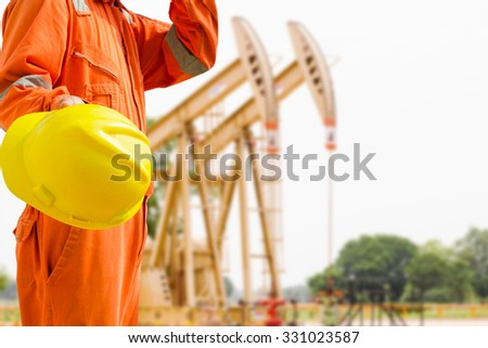 engineer hand holding yellow helmet for workers against tank farm background oil and gas process - stock photo