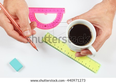 Engineer hands with a cup of coffee and a pencil - stock photo