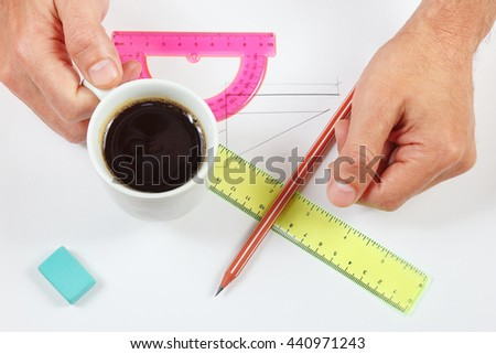 Engineer hands with a cup of coffee over a workplace - stock photo