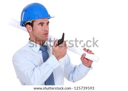 Engineer holding a rolled-up plan and speaking into a walkie-talkie - stock photo